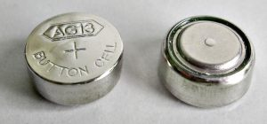 Button Battery Lawyer in Texas: Top and bottom of a small button battery.